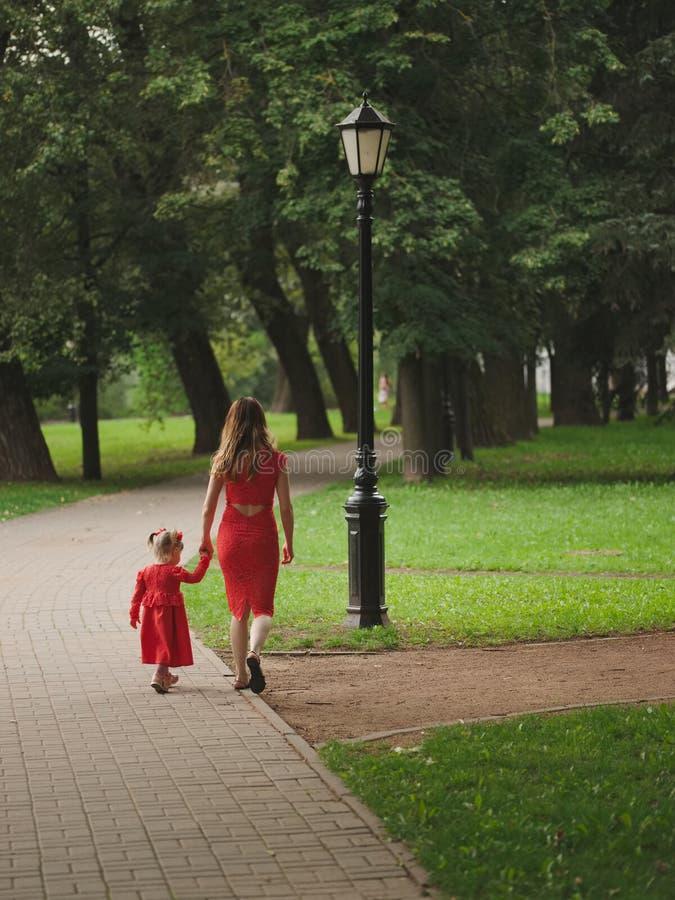 有走在夏天公园的母亲的女孩 库存图片