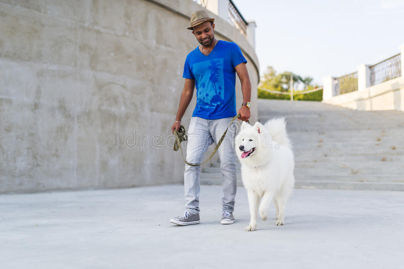 有走在夏天城市公园的萨莫耶特人狗的愉快的亚裔人 免版税库存照片