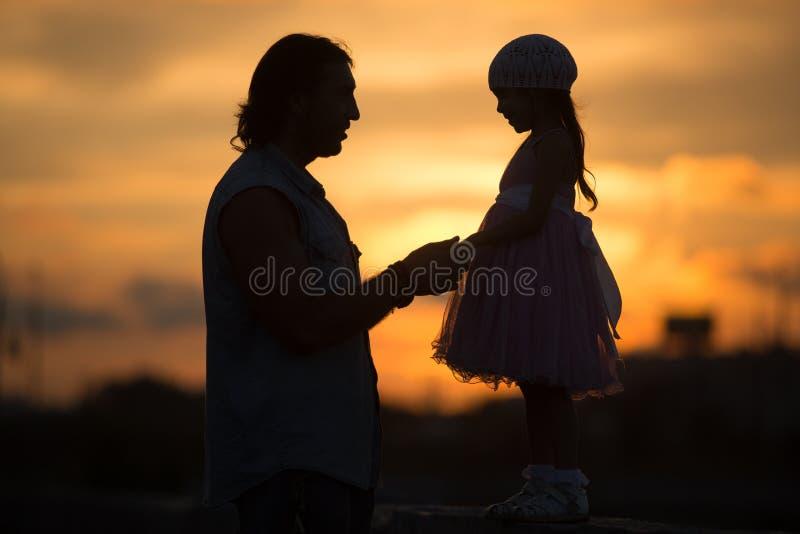 有走在日落剪影的爸爸的女孩 免版税库存图片
