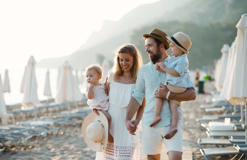 有走在海滩的两个小孩孩子的一个年轻家庭在度假夏天休假 库存照片