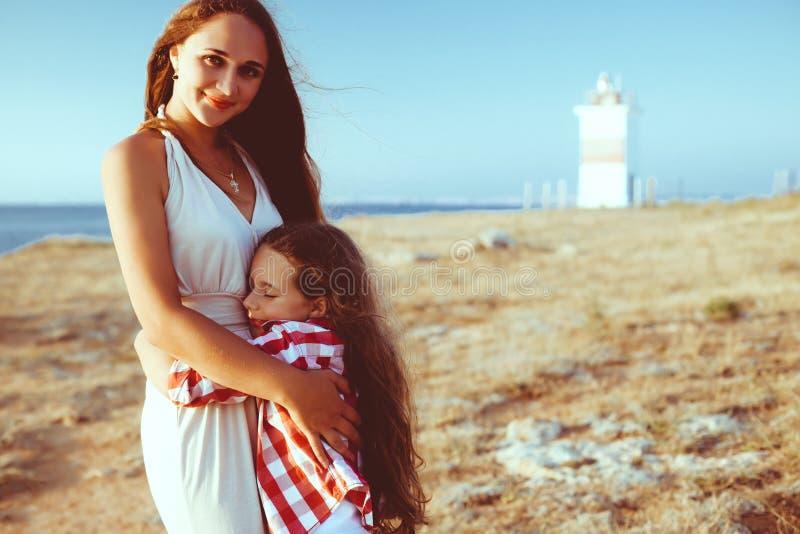 有走在海滩的妈妈的孩子 免版税图库摄影