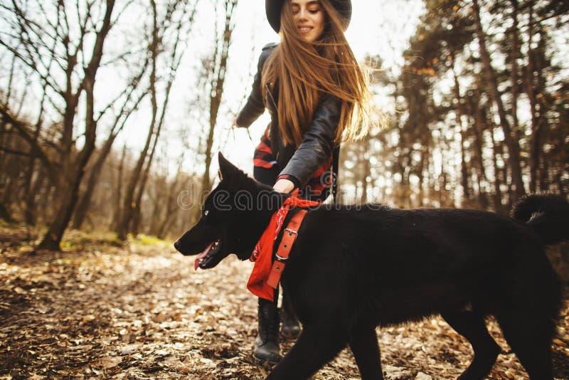 有走在秋天公园的狗的少女 女孩有美丽的黑帽会议 库存照片