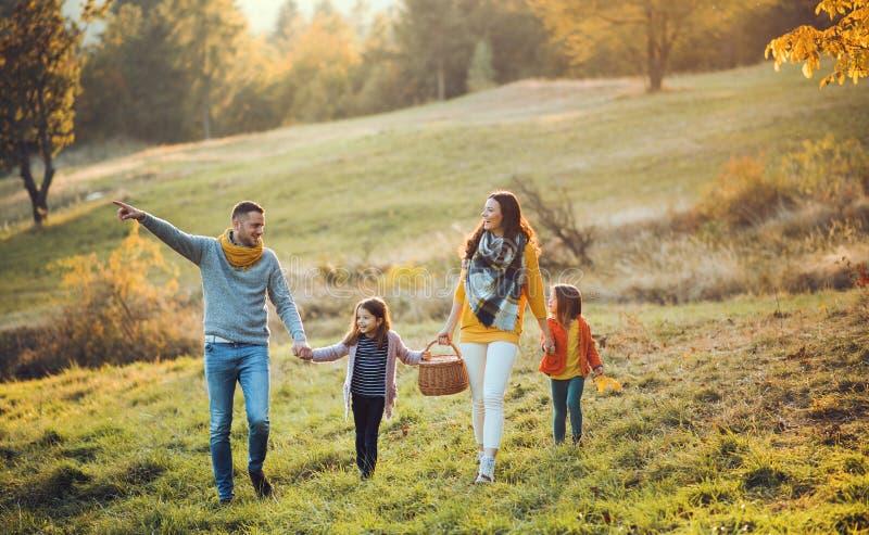 有走在秋天自然的两个小孩子的一个年轻家庭 免版税库存图片
