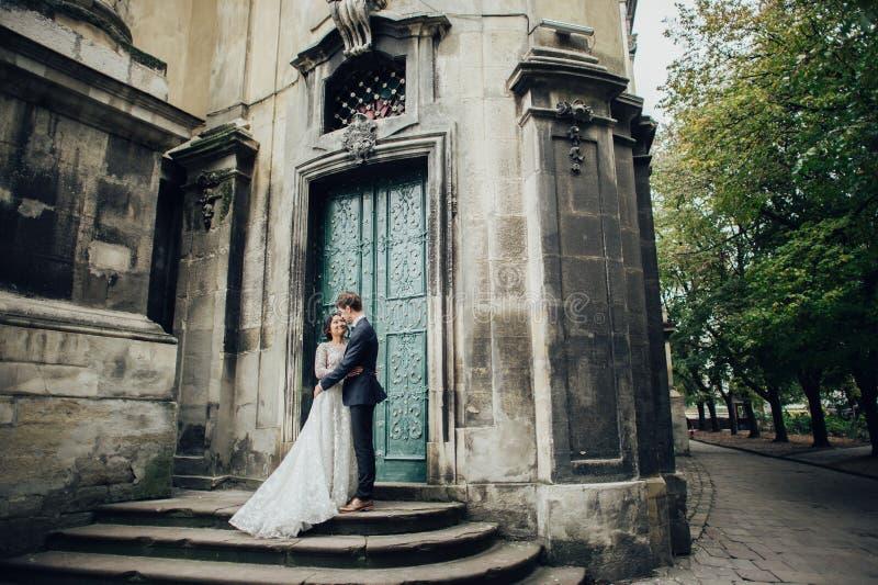 有走在老宽容大教堂附近的新郎的典雅的新娘 免版税库存图片