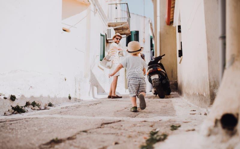 有走在镇的小孩儿子的一个父亲在度假夏天休假 免版税库存照片