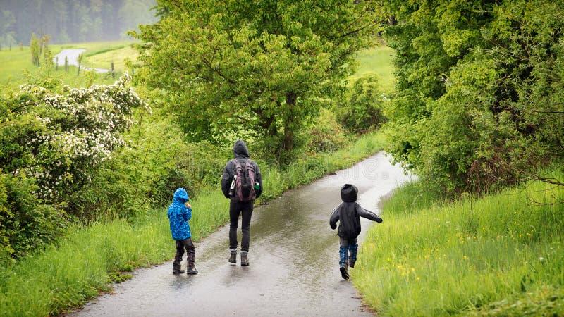 有走在雨中的孩子的父亲 库存图片
