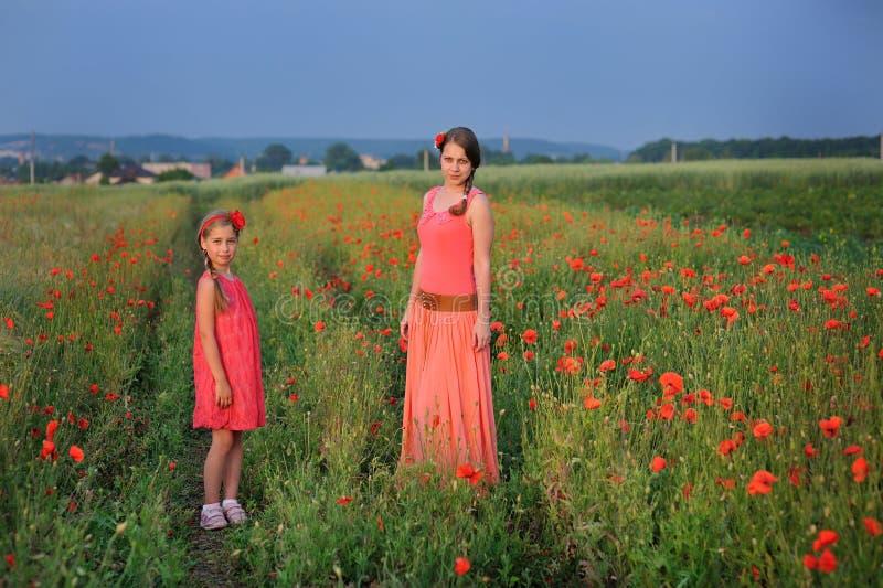 有走在鸦片领域的母亲的小女孩 免版税库存图片