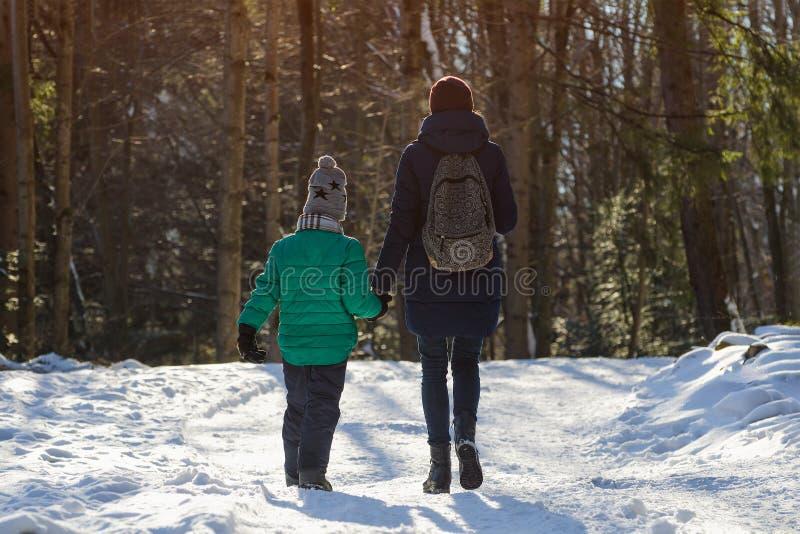 有走沿积雪的路的儿子的母亲以具球果森林冬天好日子为背景 特写镜头 图库摄影