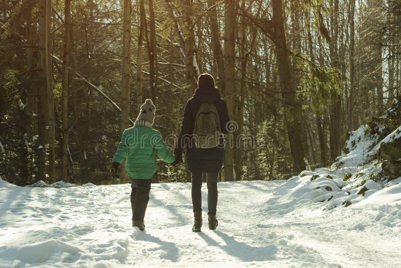 有走沿积雪的路的儿子的母亲以具球果森林冬天好日子为背景 免版税库存图片