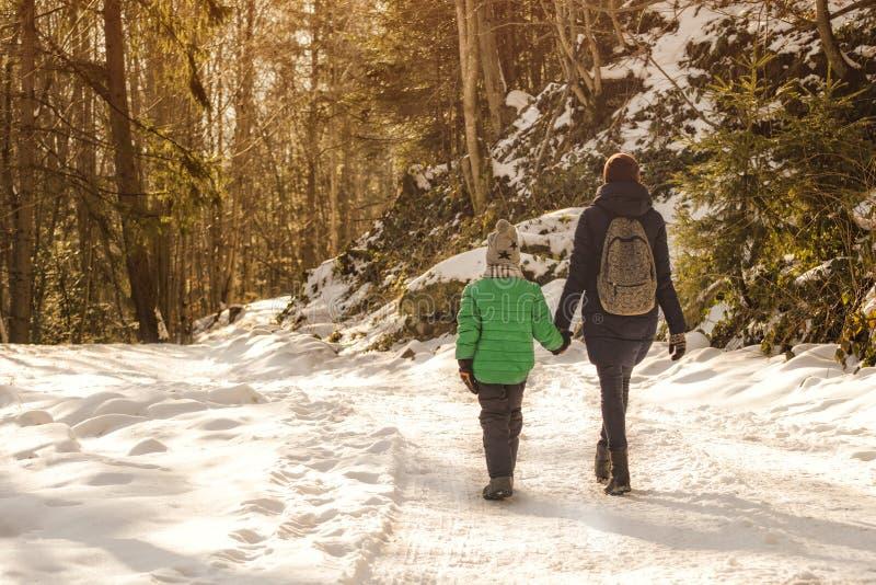 有走沿积雪的路的儿子的母亲以具球果森林和小山为背景 冬天晴天 库存图片