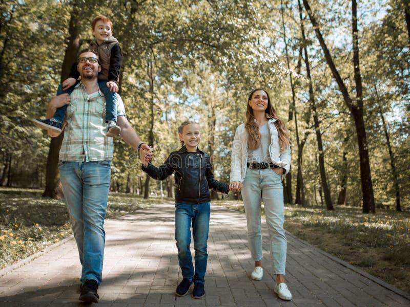 有走沿道路的孩子的家庭在城市公园 免版税库存照片