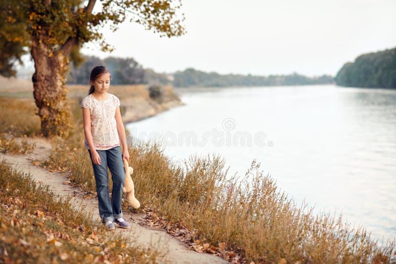 有走沿道路的玩具熊的女孩孩子在森林里在日落、美丽的河和风景 图库摄影