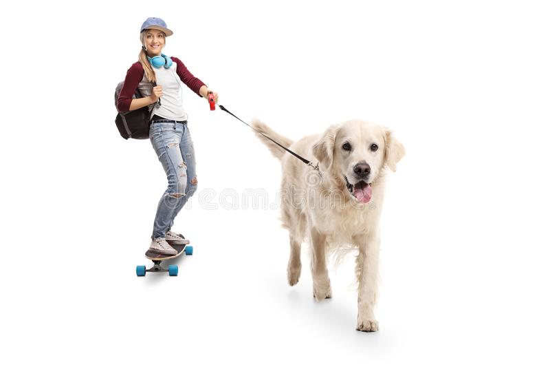 有走的背包的女性溜冰者乘坐longboard和d 免版税库存图片