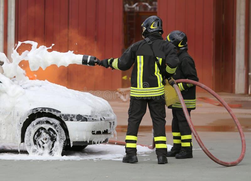 有起泡沫的火的勇敢的消防队员在以后的汽车火 库存照片