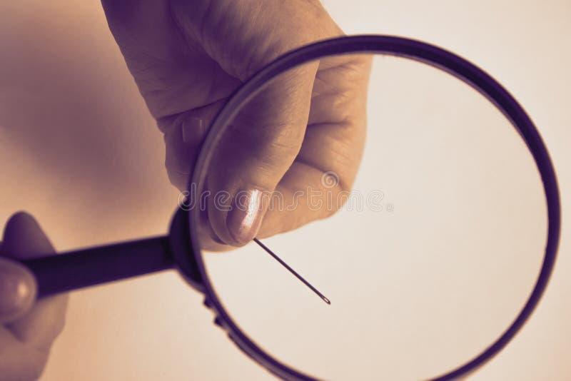 有起皱纹的手指的一名年长妇女拿着一个放大镜,并且通过透明玻璃是可看见的钢 免版税库存照片