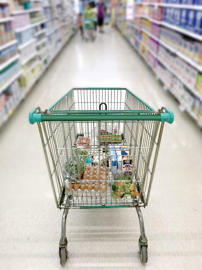 有超级市场走道的购物车和架子在迷离背景中 库存照片