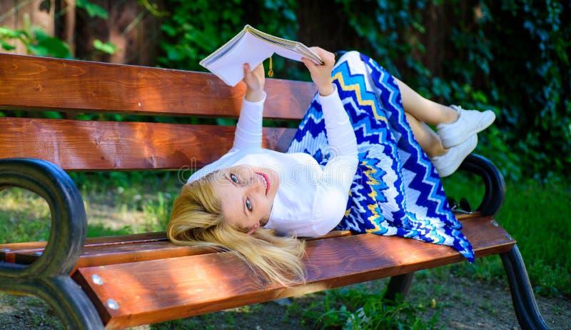 有趣的书 聪明和相当 聪明夫人放松 女孩放置放松与书,绿色自然背景的长凳公园 免版税图库摄影