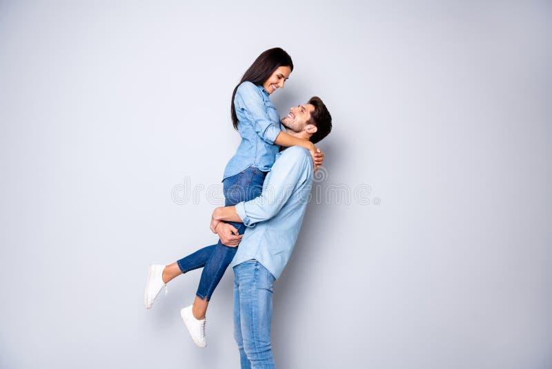 有趣的男人在初吻前抱着女人,抱着双臂,最浪漫的情侣,穿着休闲牛仔裤 库存照片