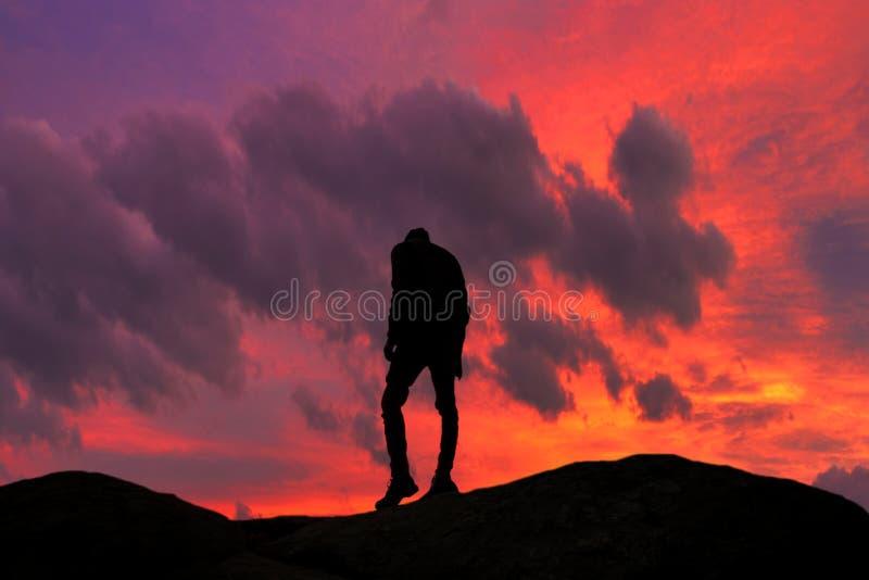 有趣的细节 上升到他的目标的一个年轻人的剪影 好的日落和红色天空在背景中 免版税库存图片