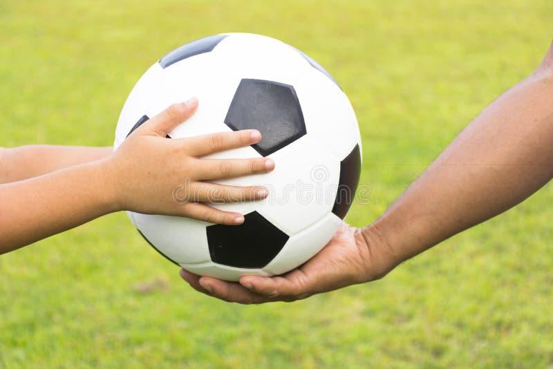 有足球的在背景绿草的孩子和教练 免版税库存图片