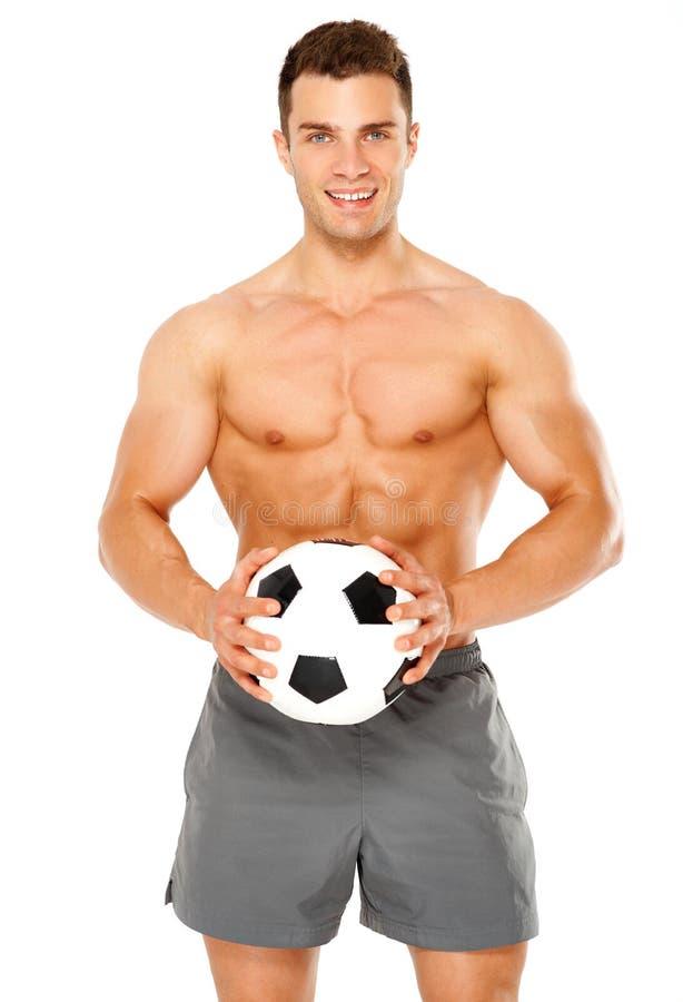 有足球的适合的肌肉人在白色 免版税库存照片