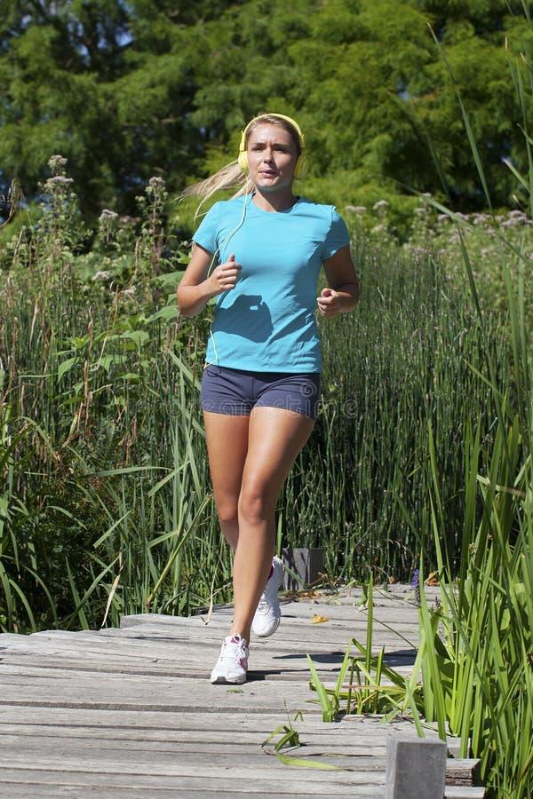 有跑为自由和耐力的音乐足迹的少妇 免版税图库摄影