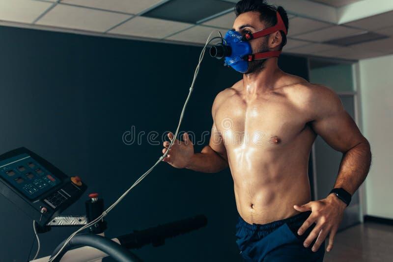 有跑在踏车的面具的适合和肌肉运动员 库存照片