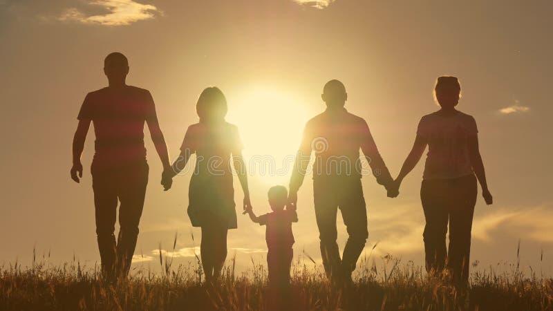 有跑在领域,在日落的剪影附近的孩子的愉快的年轻家庭 免版税库存照片