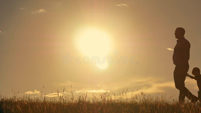 有跑在领域,在日落的剪影附近的孩子的愉快的年轻家庭 免版税库存图片