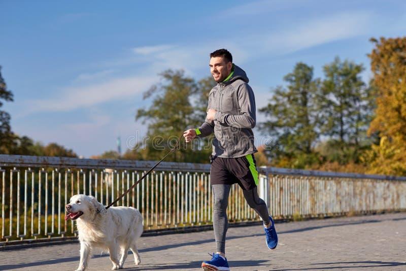有跑拉布拉多的狗的愉快的人户外 免版税库存照片