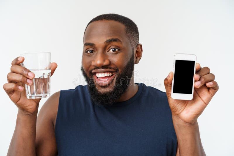 有跑的体育的非裔美国人的男性运动员体育人与手机和饮用水从玻璃 库存图片