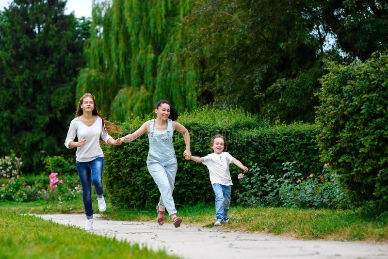 有跑的女儿和的儿子的愉快的母亲  库存图片