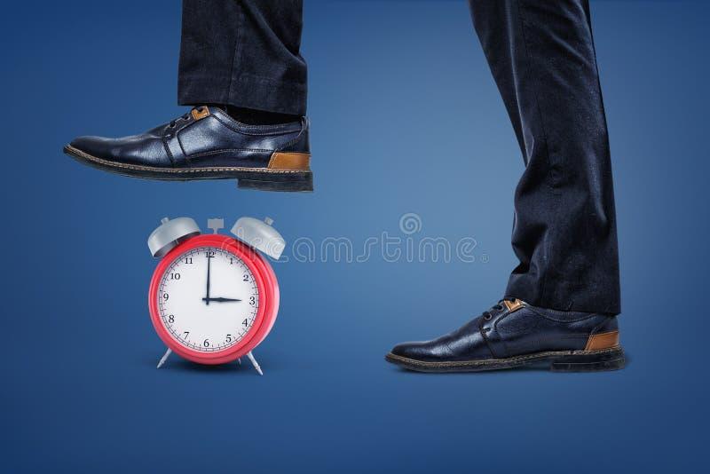 有跨步在一个红色减速火箭的闹钟上的一只脚的巨型商人s腿 免版税库存照片