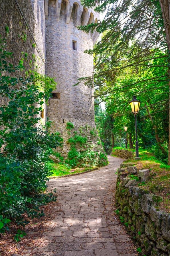 有路灯到底灯的鹅卵石道路在石头砖中世纪城堡塔附近墙壁在共和国的圣马力诺绿色公园 图库摄影