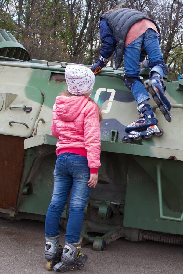 有路辗的两个青少年的女孩在战争布雷得里作战车辆 免版税库存图片