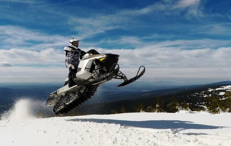 有跳跃与在山顶的一辆雪上电车的盔甲的车手人在冬天 免版税库存照片