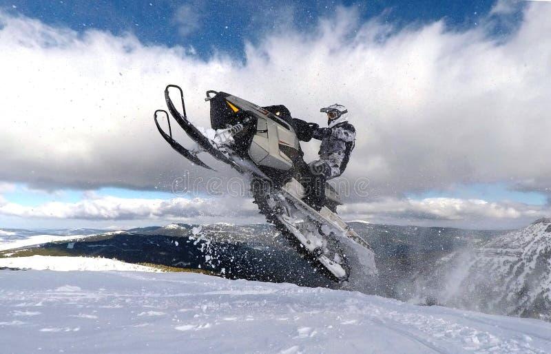 有跳跃与雪上电车的盔甲的车手人在云彩之间在冬天 免版税库存照片