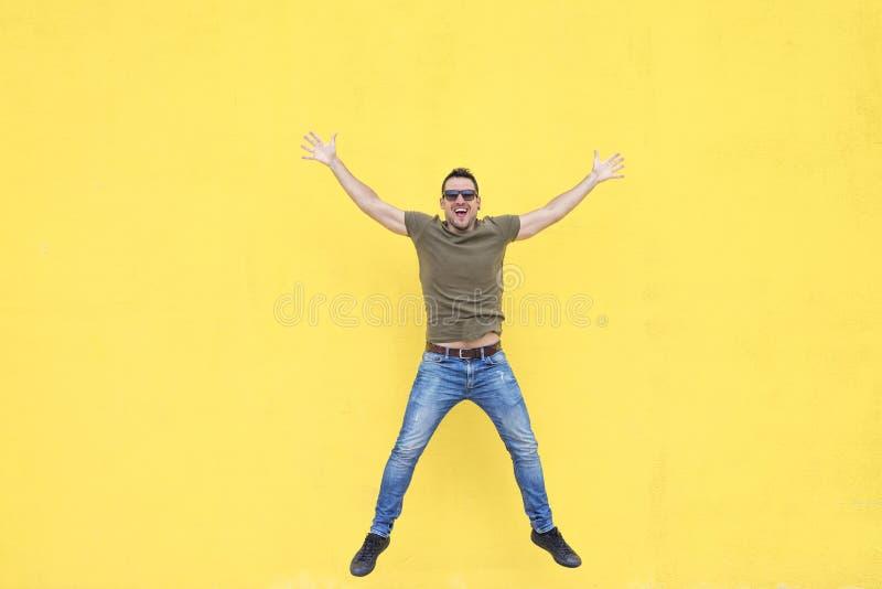 有跳跃对黄色墙壁的太阳镜的年轻人 库存图片
