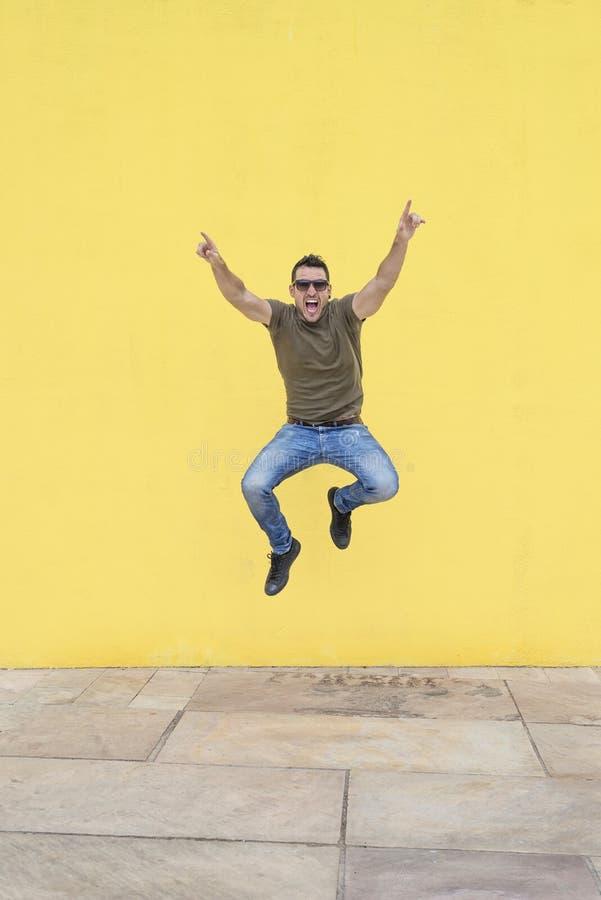 有跳跃对黄色墙壁的太阳镜的年轻人 图库摄影