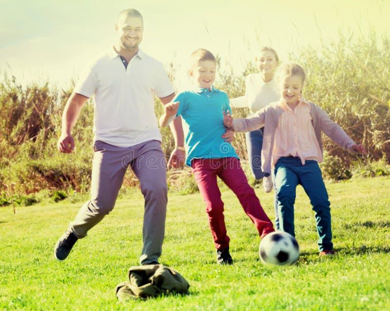 有踢足球的两个孩子的父母 库存照片