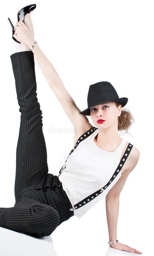 有躺下的黑帽会议的俏丽的妇女 免版税库存照片