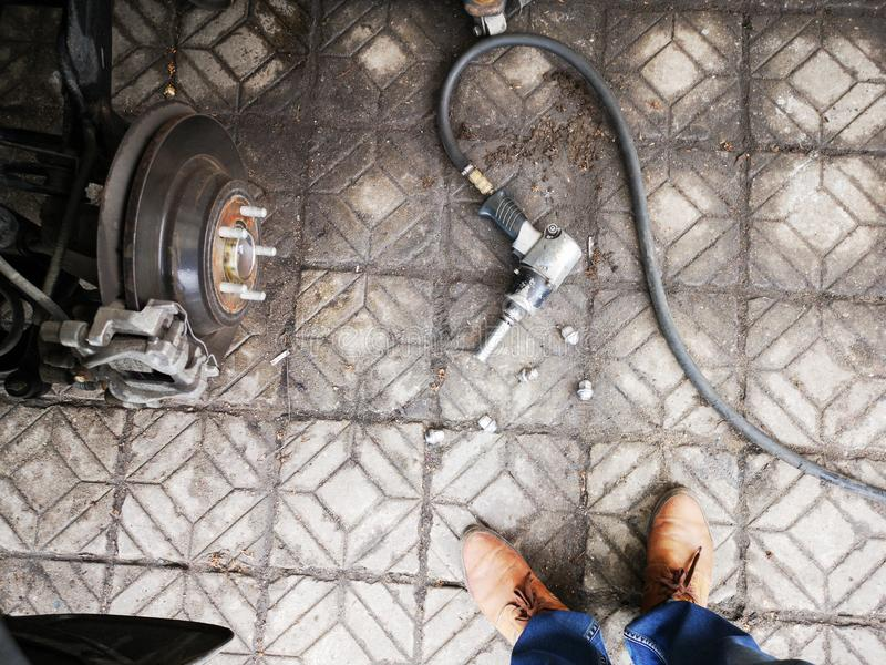 有车胎坚果的气动力学的板钳在具体在旁边地板汽车用千斤顶压出或拔出器拔出和修理车胎的生锈的金属片断  免版税库存图片