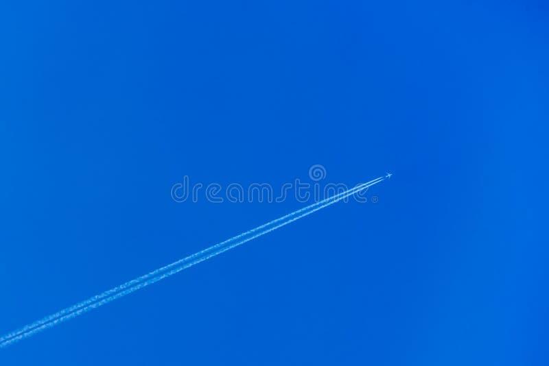 有转换轨迹的飞机在天空蔚蓝 免版税库存照片