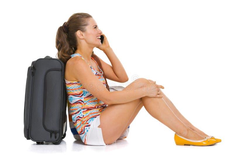 有轮子袋子谈的手机的旅游妇女 免版税图库摄影