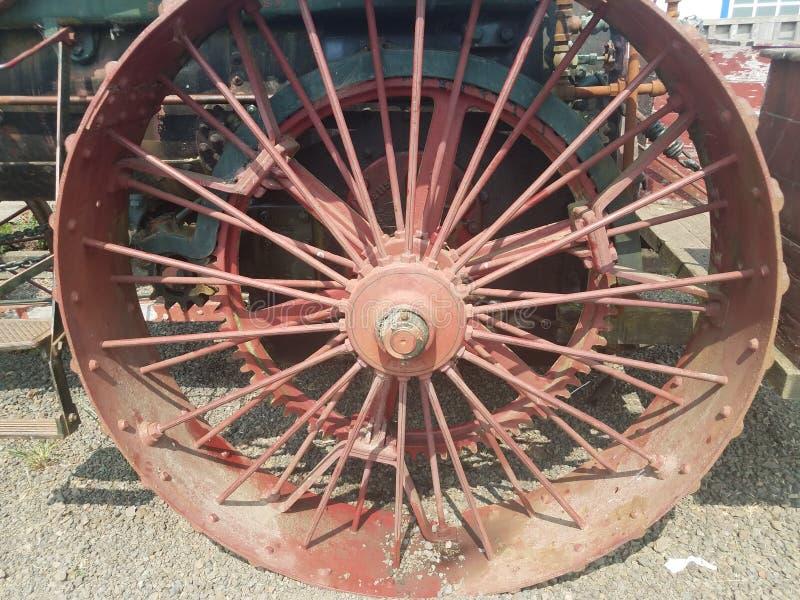 有轮幅的老红色金属轮子在车 库存图片