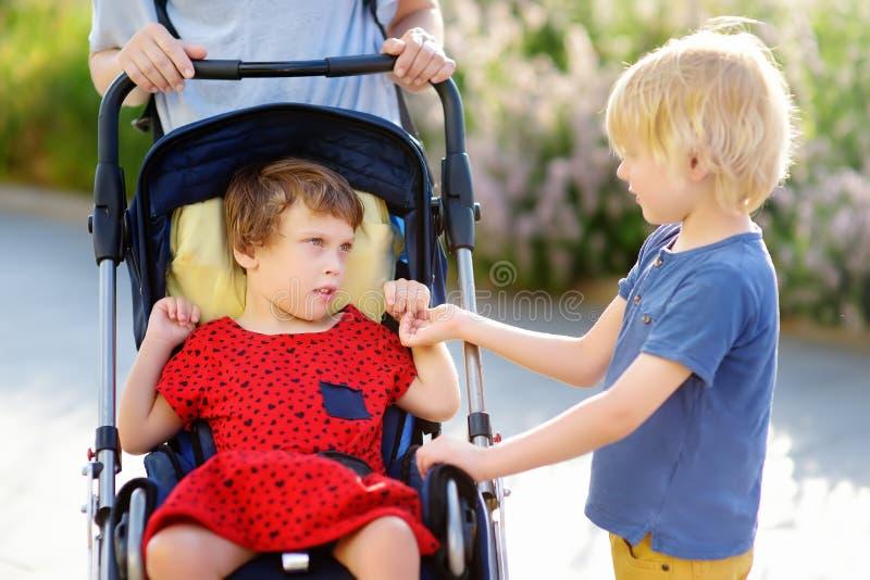 有轮椅的走在公园夏天的一个男孩和一个残疾女孩的一名妇女 儿童大脑麻痹 与残疾孩子的家庭 免版税图库摄影