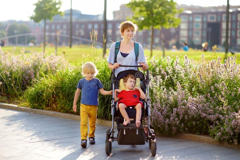 有轮椅的走在公园的一个男孩和一个残疾女孩的妇女在夏天 儿童大脑麻痹 与残疾孩子的家庭 免版税库存照片