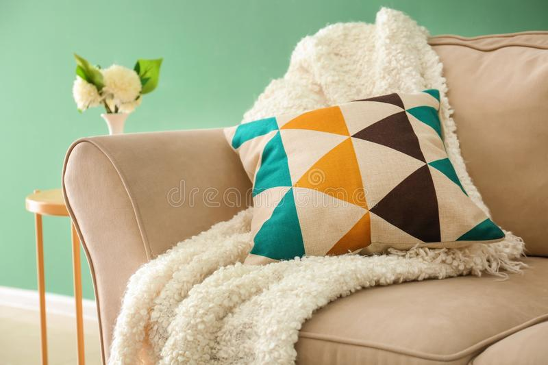 有软的枕头和格子花呢披肩的舒适的沙发在颜色墙壁附近 免版税库存图片