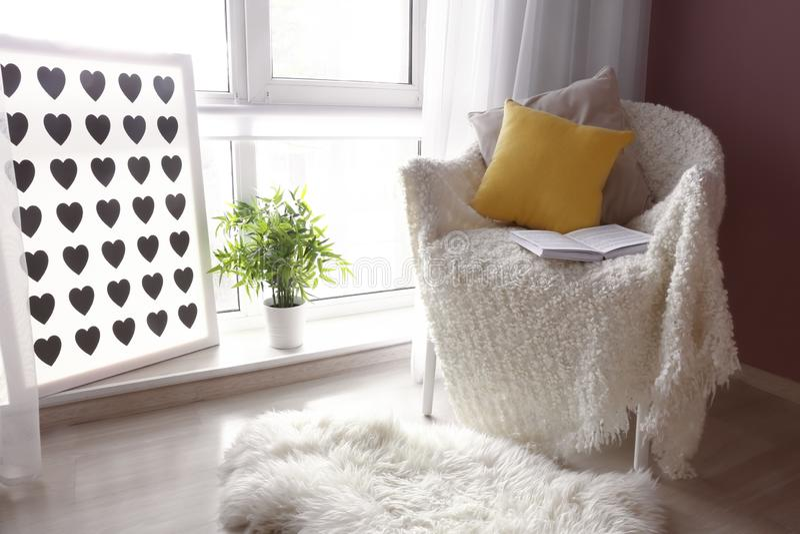 有软的格子花呢披肩和开放书的舒适扶手椅子在窗口附近在屋子里 免版税库存图片