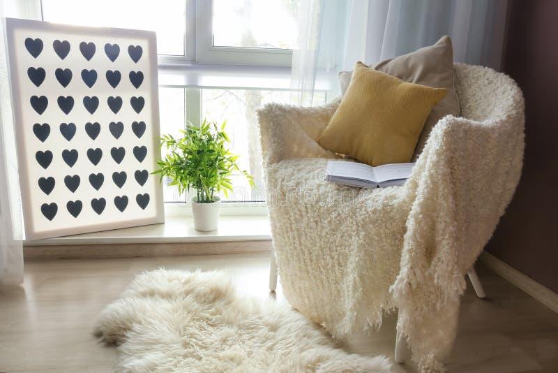 有软的格子花呢披肩和开放书的舒适扶手椅子在窗口附近在屋子里 免版税库存照片